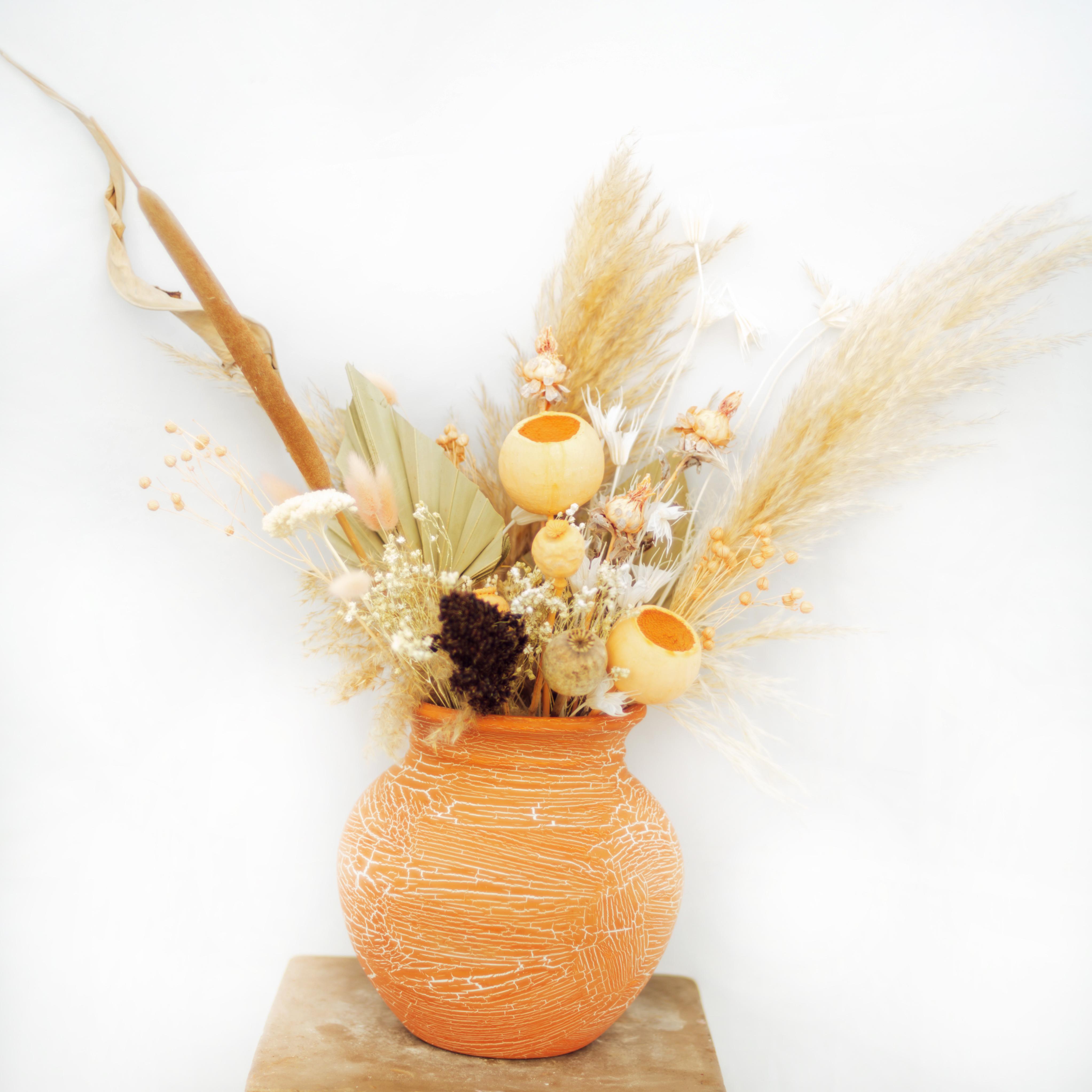 Dried flowers in handmade orange pot